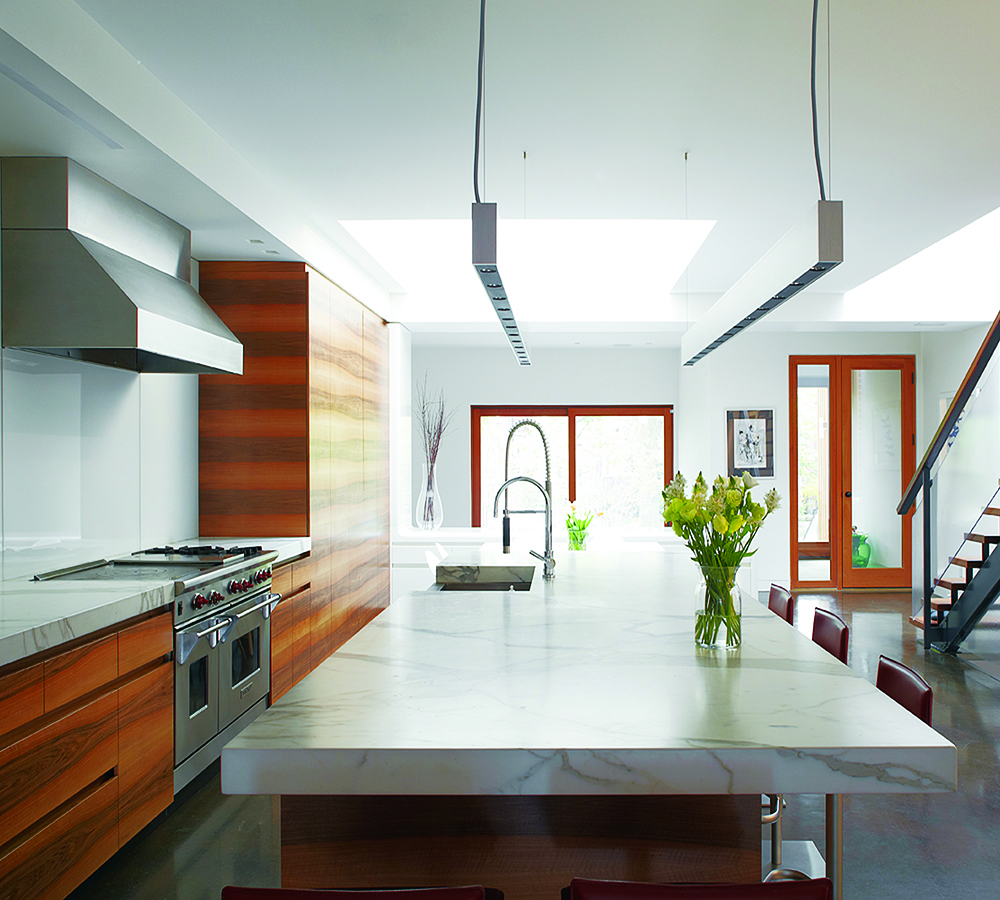 The kitchen's book-matched wood grain, Carrera marble– topped island and thin suspension lights elongate the space.