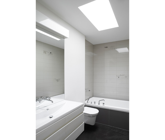 The custom vanity is finished in white automobile paint to thwart fingerprints.