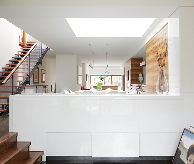 Glossy white cabinetry, dividing the kitchen and media room, stores tableware and audiovisual equipment.