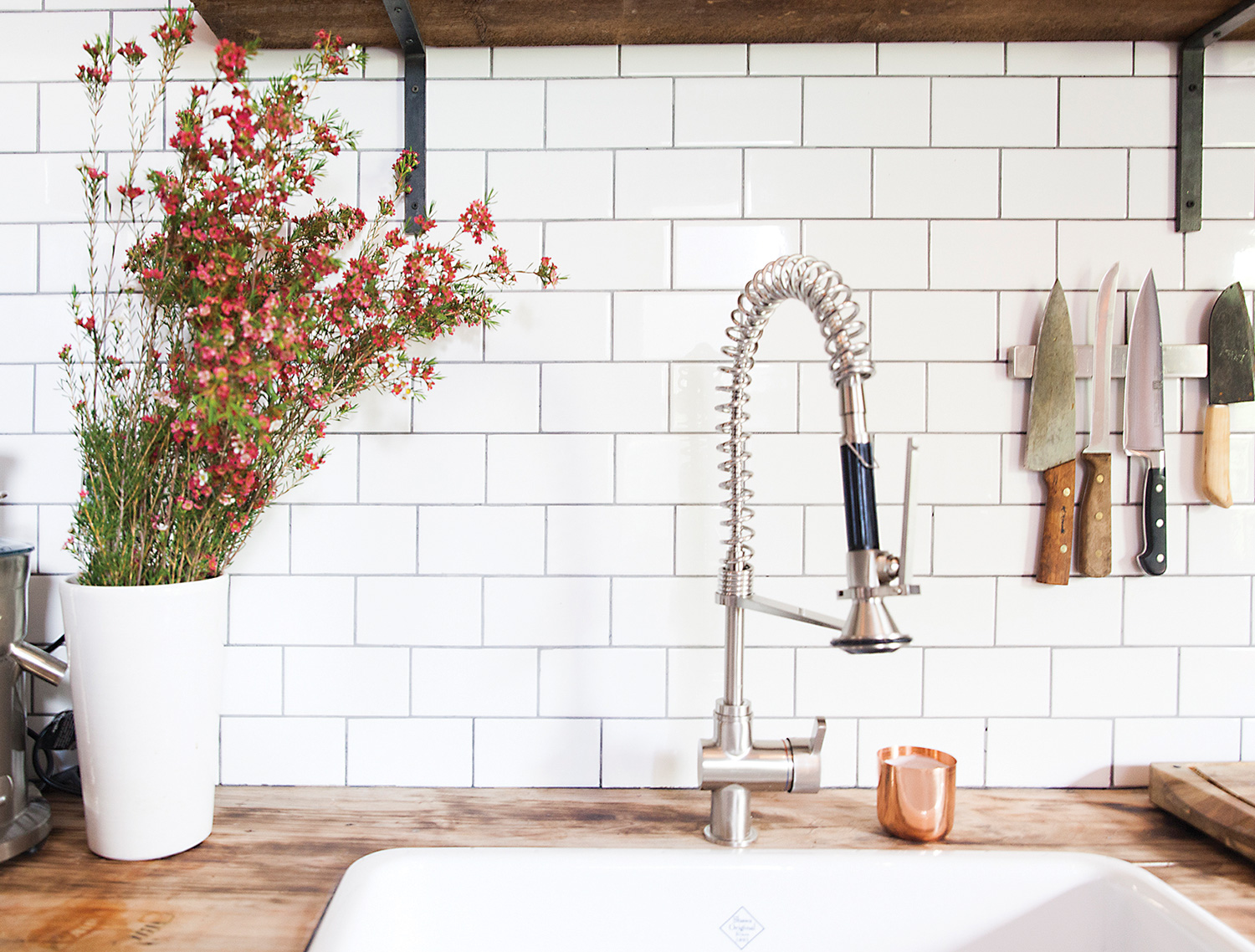 White subway tile (from Saltillo Imports) with grey grout covers two walls in the kitchen. Oak shelves are hoisted on industrial-strength brackets; sink from Roman Bath Centre.