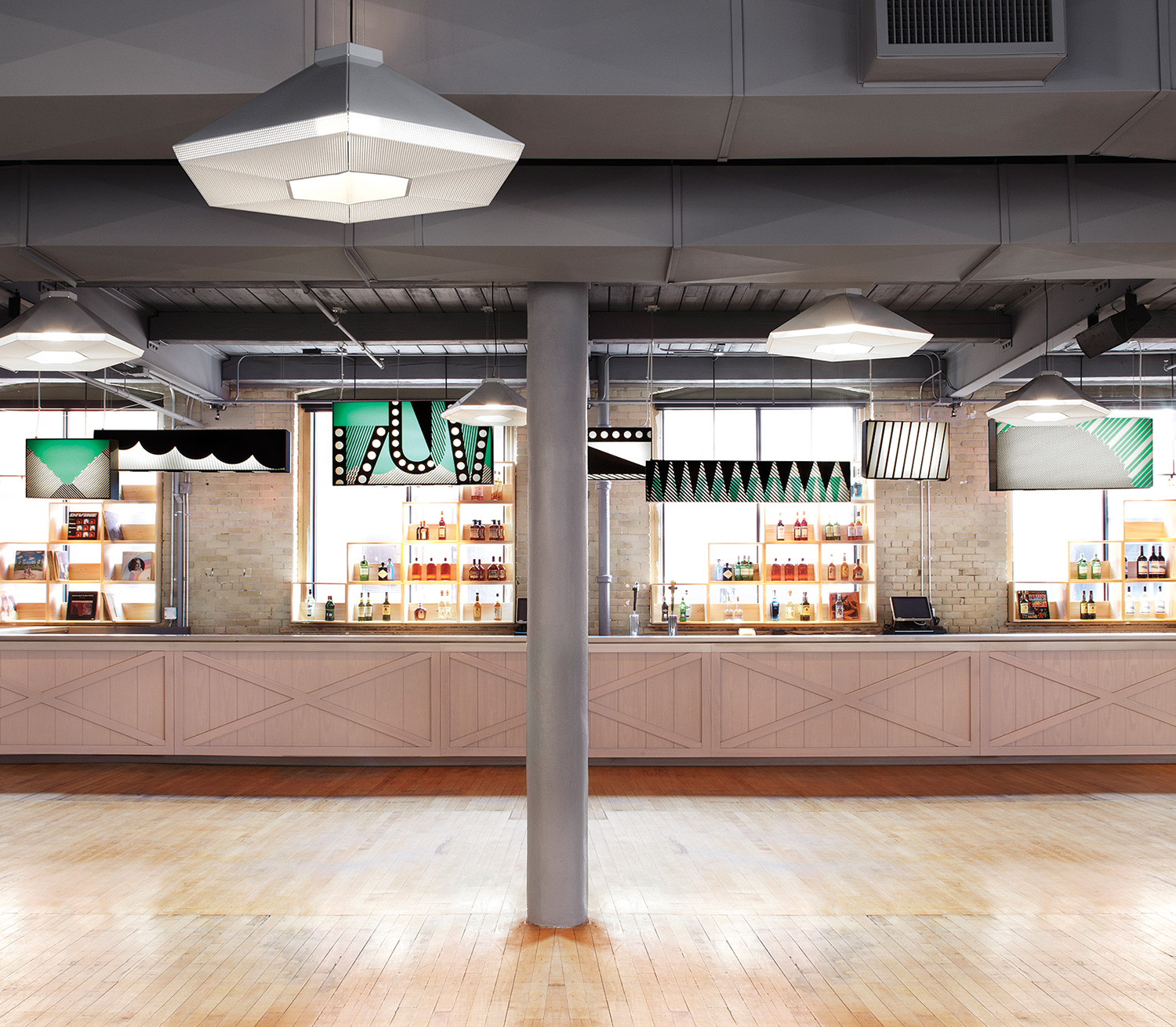 2nd Floor (Event Space): Vaguely recalling a marketplace, vendor stalls typically made from reclaimed wood are replaced by a bespoke, 11-metre-long bar clad in stained Carolina pine. Instead of flashing signs, flags and canopies are graphic-laden light boxes (by Ben Motz and made by Kubik) and hexagonal pendants made of perforated metal (by Jonathan Sabine).