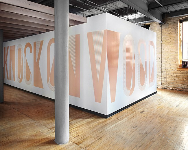 "2nd Floor (Event Space): A 24-square-metre vinyl wall  that reads ""Knock on wood"" (by Ben Motz) smartly conceals the bathrooms and coat check."
