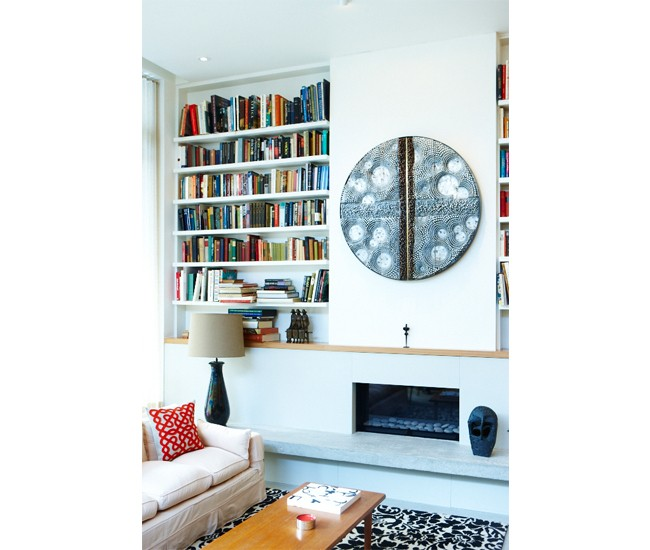 Floating white shelves, inset on either side of the natural gas fireplace, house but a portion of Helene's books. Nail art by David Partridge; rug from Elte. Photo by Naomi Finlay.
