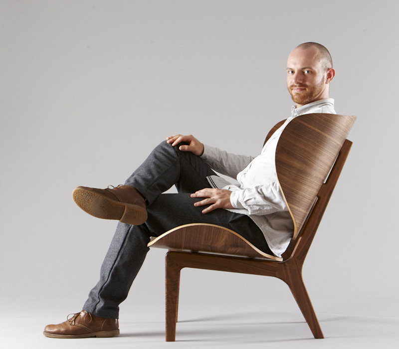Furniture designer Chris Fieldhouse in his Finn Chair, made with a digitally cut solid walnut frame and multi-curve plywood seat