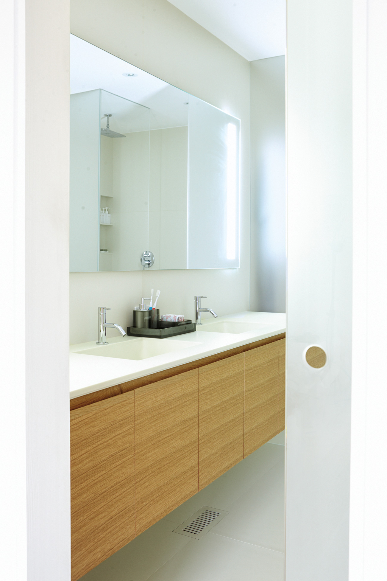 A glass pocket door opens to the master bath. The oak vanity's countertop, with built-in sinks, is Corian. Mirror by Lumidesign; accessories from Ginger's.