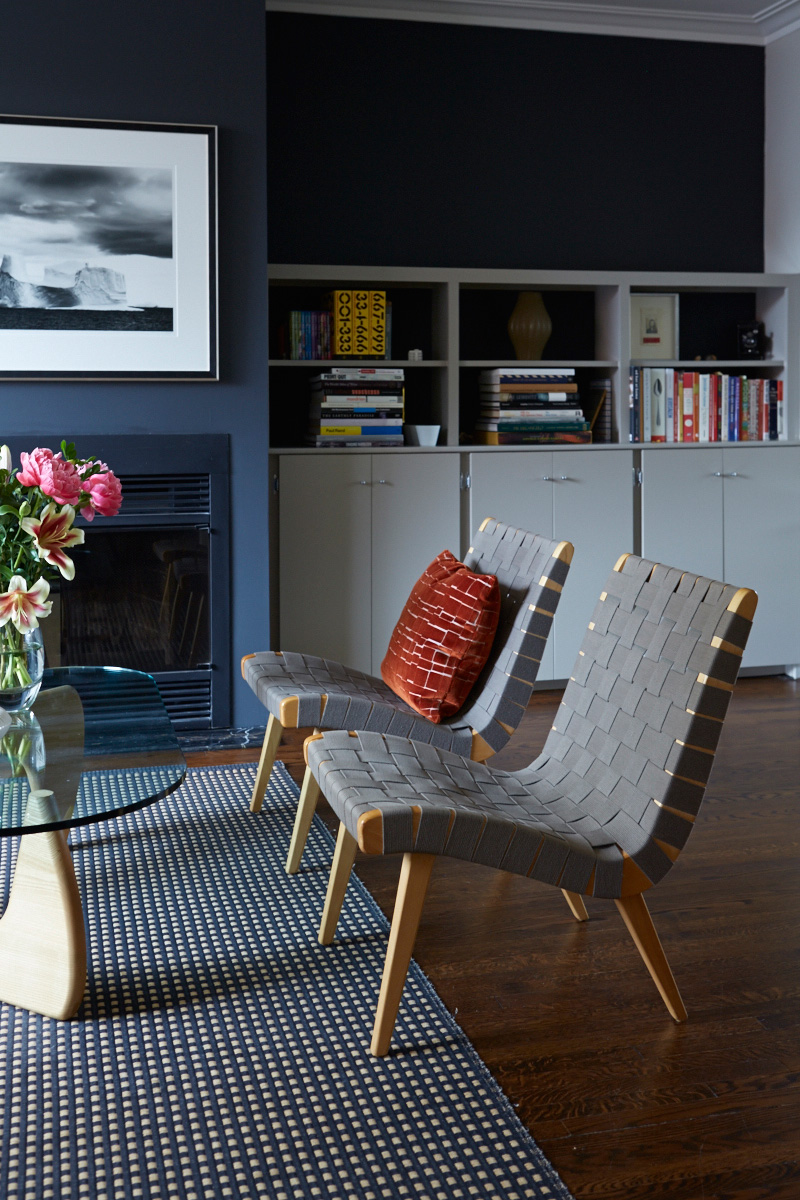 The front room's fireplace is surrounded by built-in cabinets, which along with the hardwood flooring are original. Noguchi table and Knoll Risom chairs available at DWR; rug from Klaus.