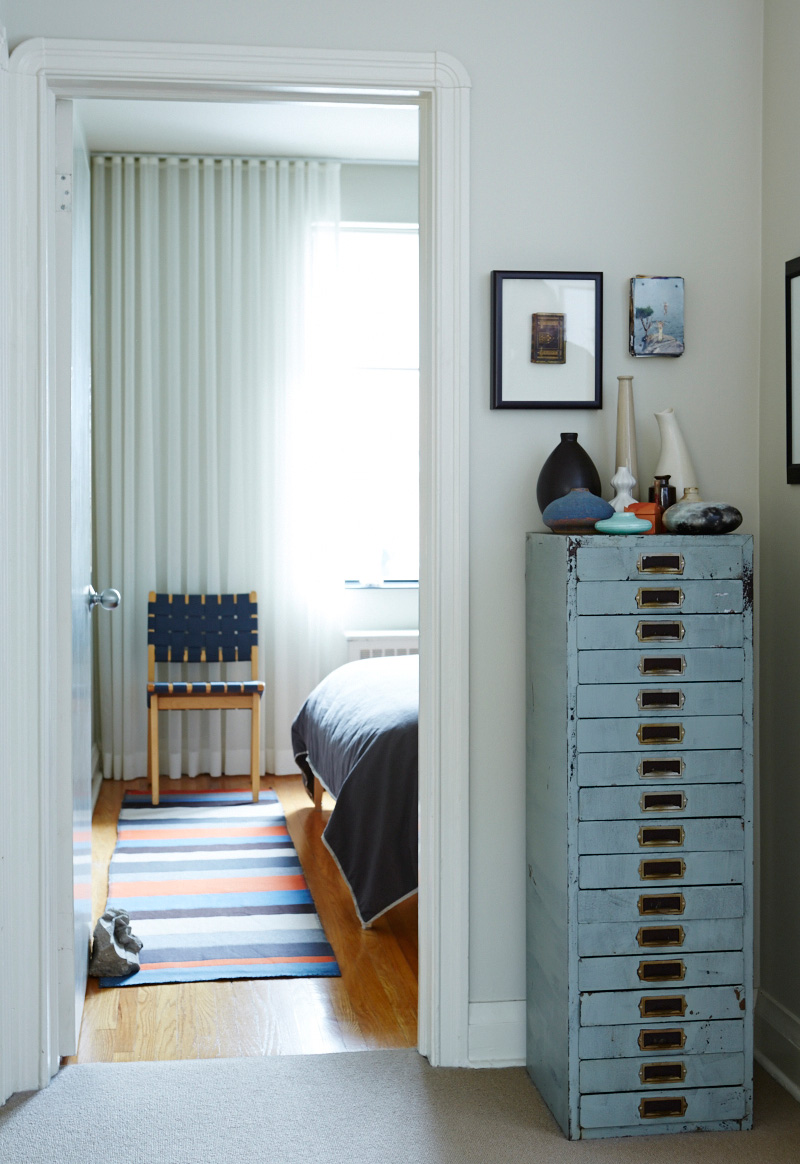 A vintage watch-maker's filing cabinet is topped with a medley of vases; an heirloom, shadow-boxed Bible hangs on the wall. Runner by Bev Hisey.