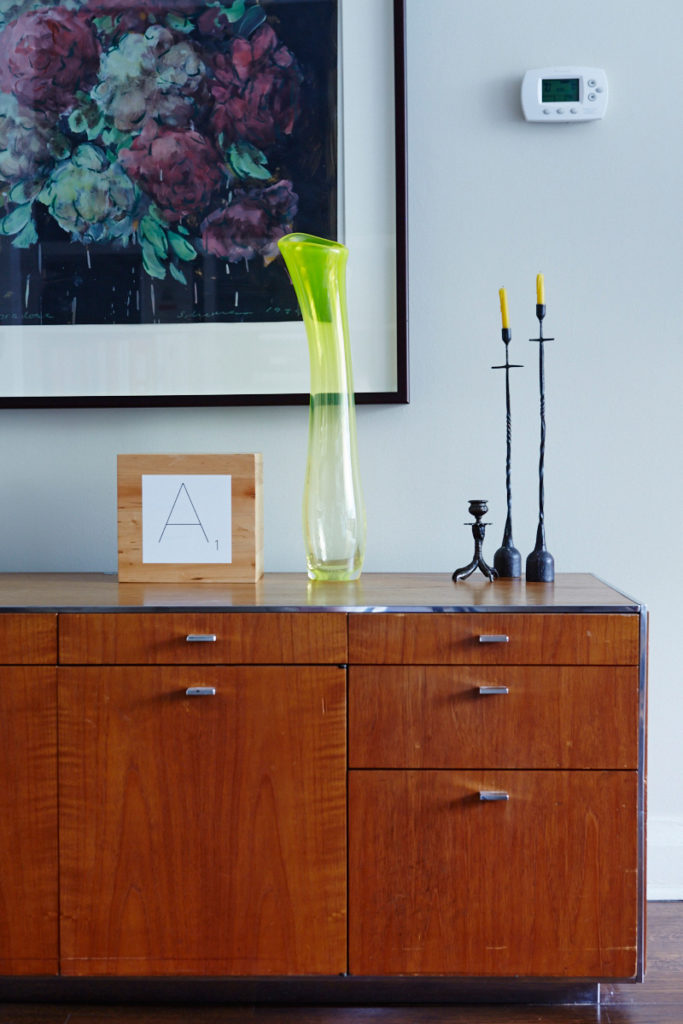 Neat arrangements of art and objets accentuate the home. A '70s credenza is topped with a vase by Jeff Goodman and iron candlesticks from Hollace Cluny. Painting by Tony Sherman.