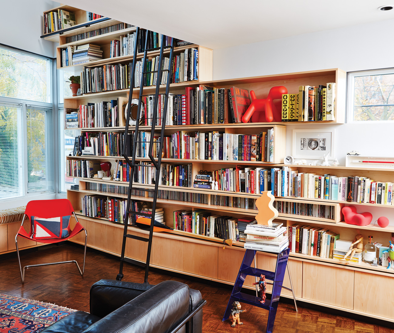 The structure, made of 15 maple boxes that extend to the house's rear entrance, ends in a benched reading nook. Chair and pillows, DWR; step ladder and Magis puppy, Quasi Modo; paddle, Contact Voyaging Co.; Kaiju toys, Studio Brillantine.
