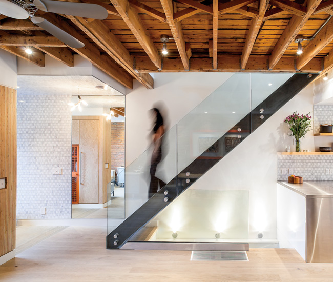 An open-tread staircase by Space Furniture and a stretch of exposed rafters separate the east-facing main entrance from the kitchen.