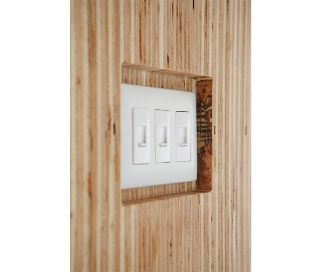 The wall surrounding reclaimed lockers conceals wiring and a mechanical shaft. Made from the guts of IKEA cabinets and clad in plywood, the light switch's custom inset sits half an inch deep.