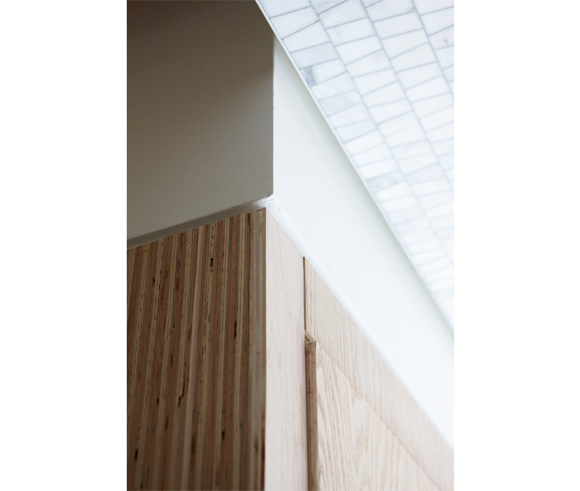 A half-inch reveal separates the foyer's plywood-clad closet from the bulkhead and tiled ceiling. The drywall, with a dental-like reveal around the rafters, gives the ceiling a clean finish.