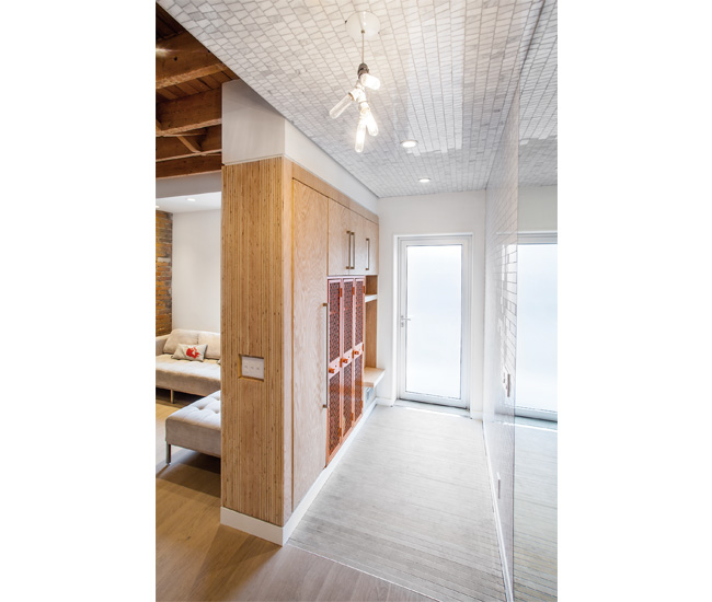 Marble mosaic tile runs up one wall and across the ceiling to delineate the foyer. The aluminum entrance grate has a pan underneath to catch water and grit.