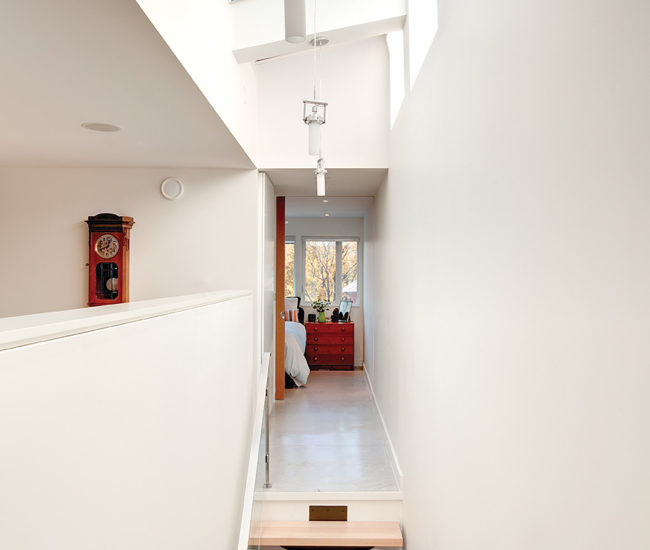 The stairwell is lit by three remote-controlled skylights by Inline Windows. Boomerang pendants from Sistemalux.
