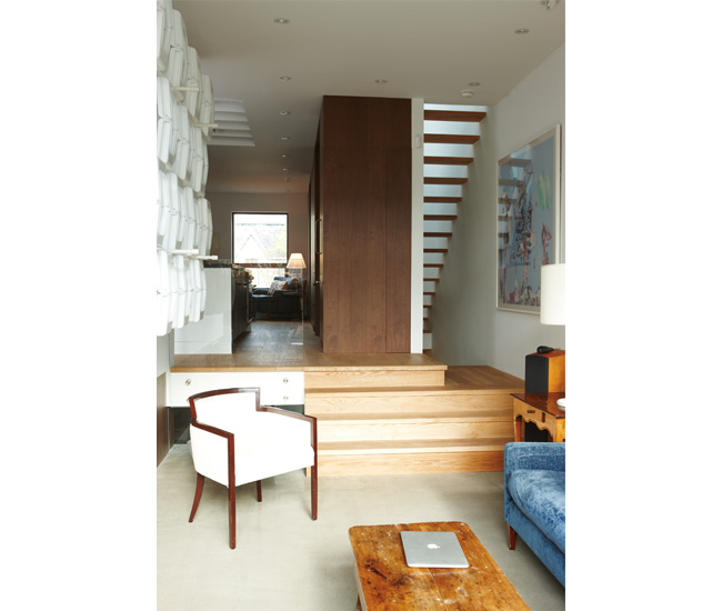 Both ends of the house can be seen through the open-riser staircase. The walnut kitchen unit conceals appliances and utilities.