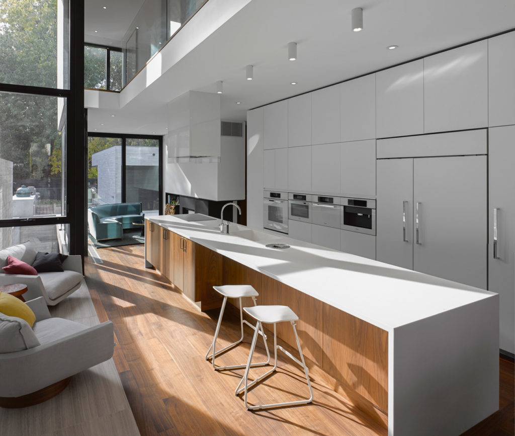 Walnut flooring and built-ins warm the cool interior. Lacquered cabinetry by O'Sullivan Millwork houses Miele's Brilliant White appliances; the five-metre-long island is topped in Corian. Photo by Ben Rahn /A-Frame.