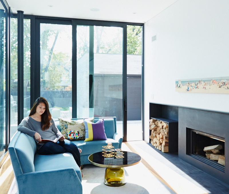 Three-metre-high glass walls with sliding doors, by Applewood Glass & Mirror, lead from the living room to the deck. Fireplace by Stuv; sofa, rug and table from Avenue Road; print by Patrick Lajoie from Art Interiors; purple pillow by Bev Hisey. Photo by Naomi Finlay.