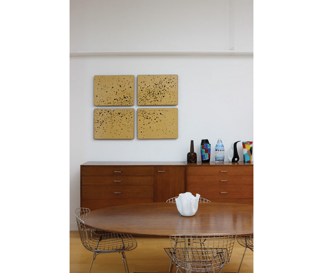 A cluster of postwar Italian glass sits on top of a George Nelson credenza. The art by Christina Meynell is made from four school desktops.