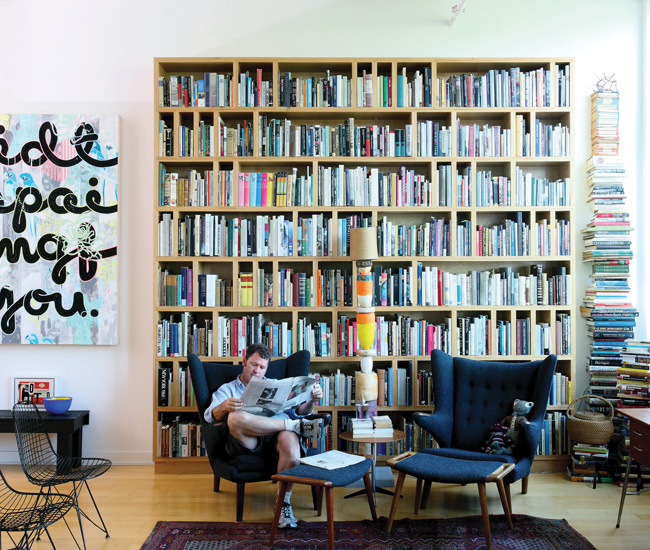 """Prokopow estimates he lives with more than 4000 books that cover art, architecture and design history, urban planning, cultural theory, plus hundreds of titles on etiquette, cooking and table setting. The painting on the wall by Emmy Skensved is titled """"I did this painting for you."""""""