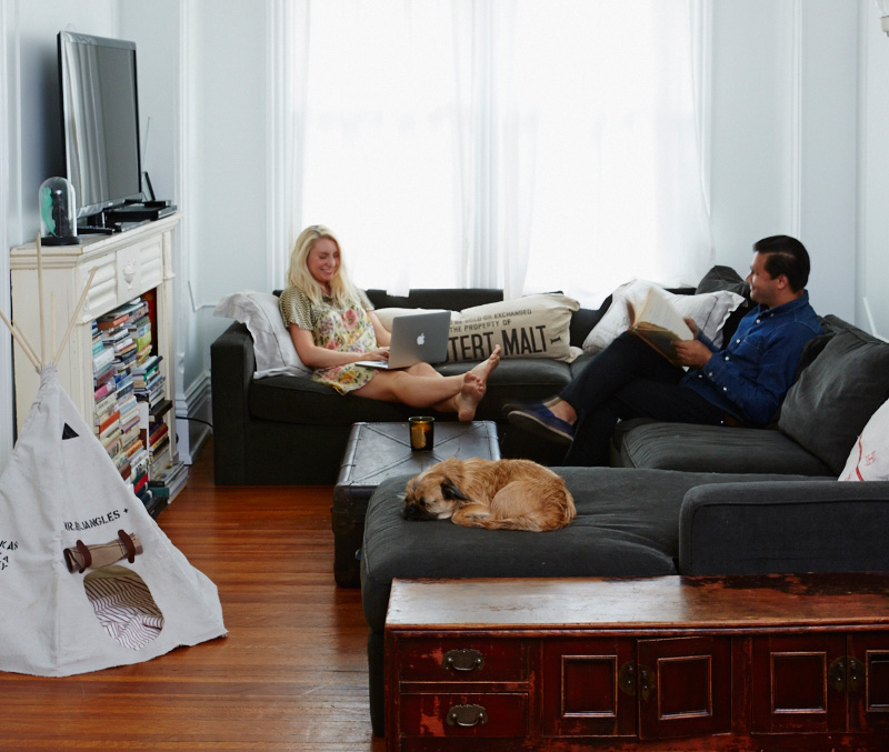 A sectional from Art Shoppe, an antique credenza, a turfed trunk and a fireplace packed with books fill the living room.