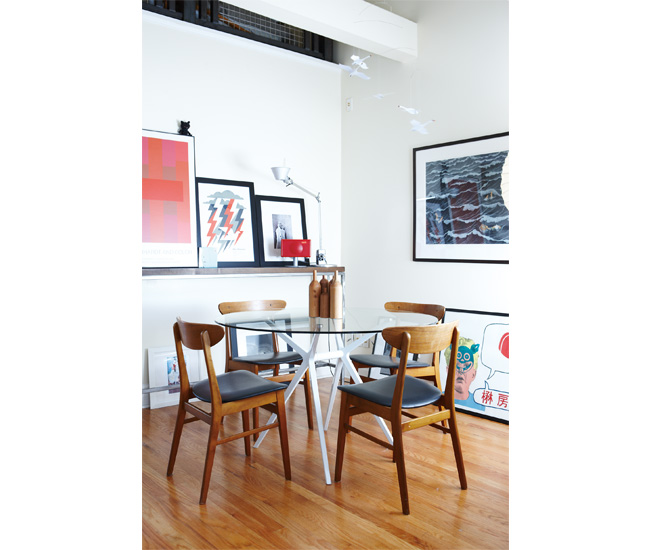 2 Ban technology. A DesignRepublic table and antique chairs are circled by even more local art, including a Doublenaut print (middle of shelf). Photo by Naomi Finlay.