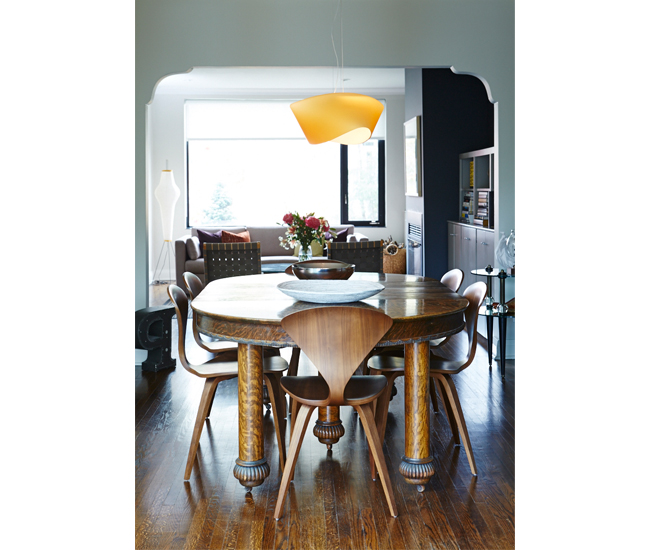 8 Play up historic details. The scalloped doorway – original to the Arts and Crafts home – frames views front to back. Cherner chairs circle an antique oak dining table; a frosted fixture by Foscarini hangs above. Photo by Naomi Finlay.