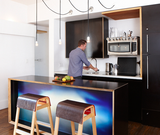 Cabinetry is made with formply – Baltic Birch plywood treated with black epoxy. A photo transfer on vinyl brightens the island.
