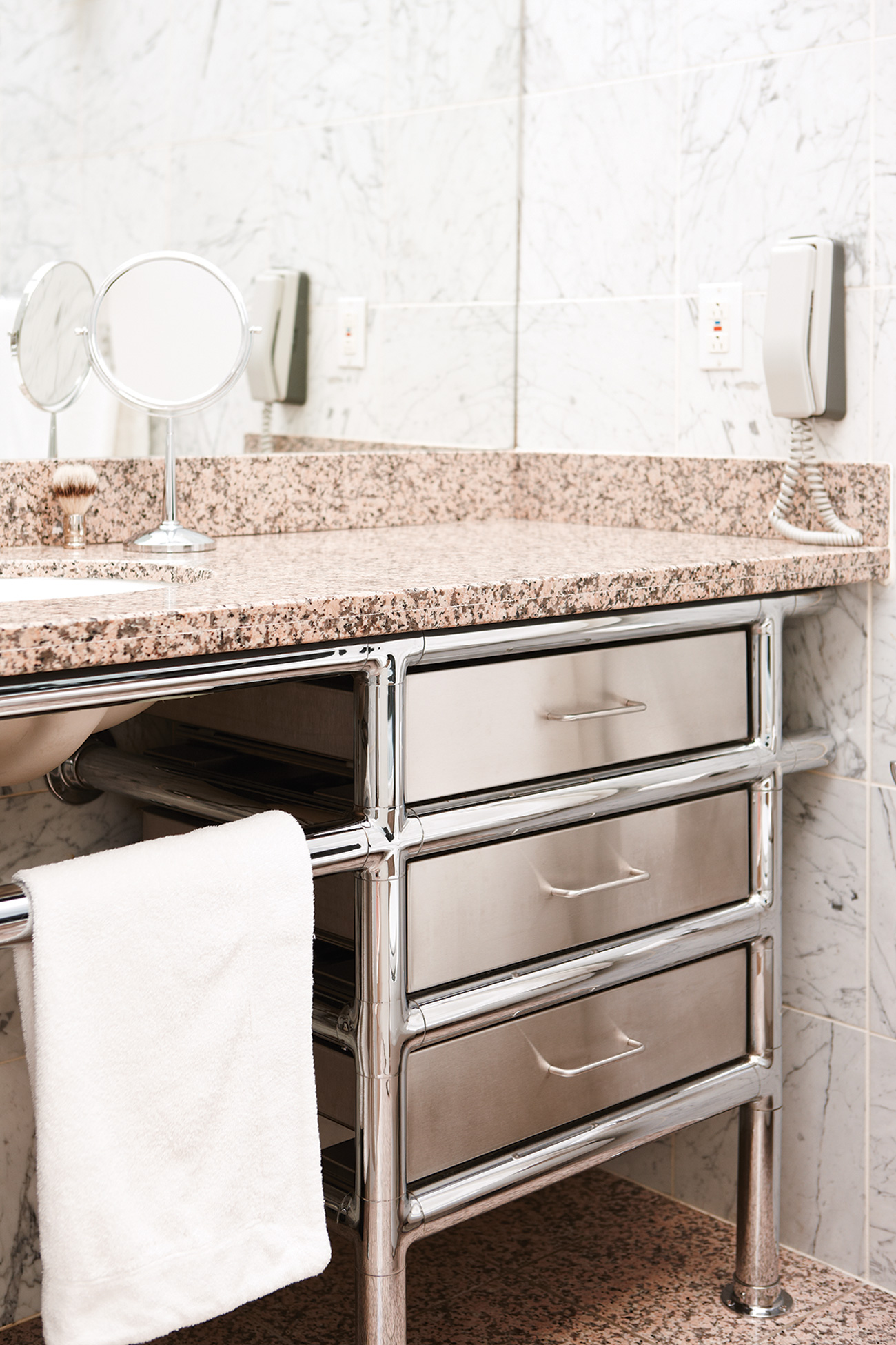 The steel-tube vanity in the guest bathroom, renovated in 1990, is topped with granite and surrounded by floor- to-ceiling marble tile.