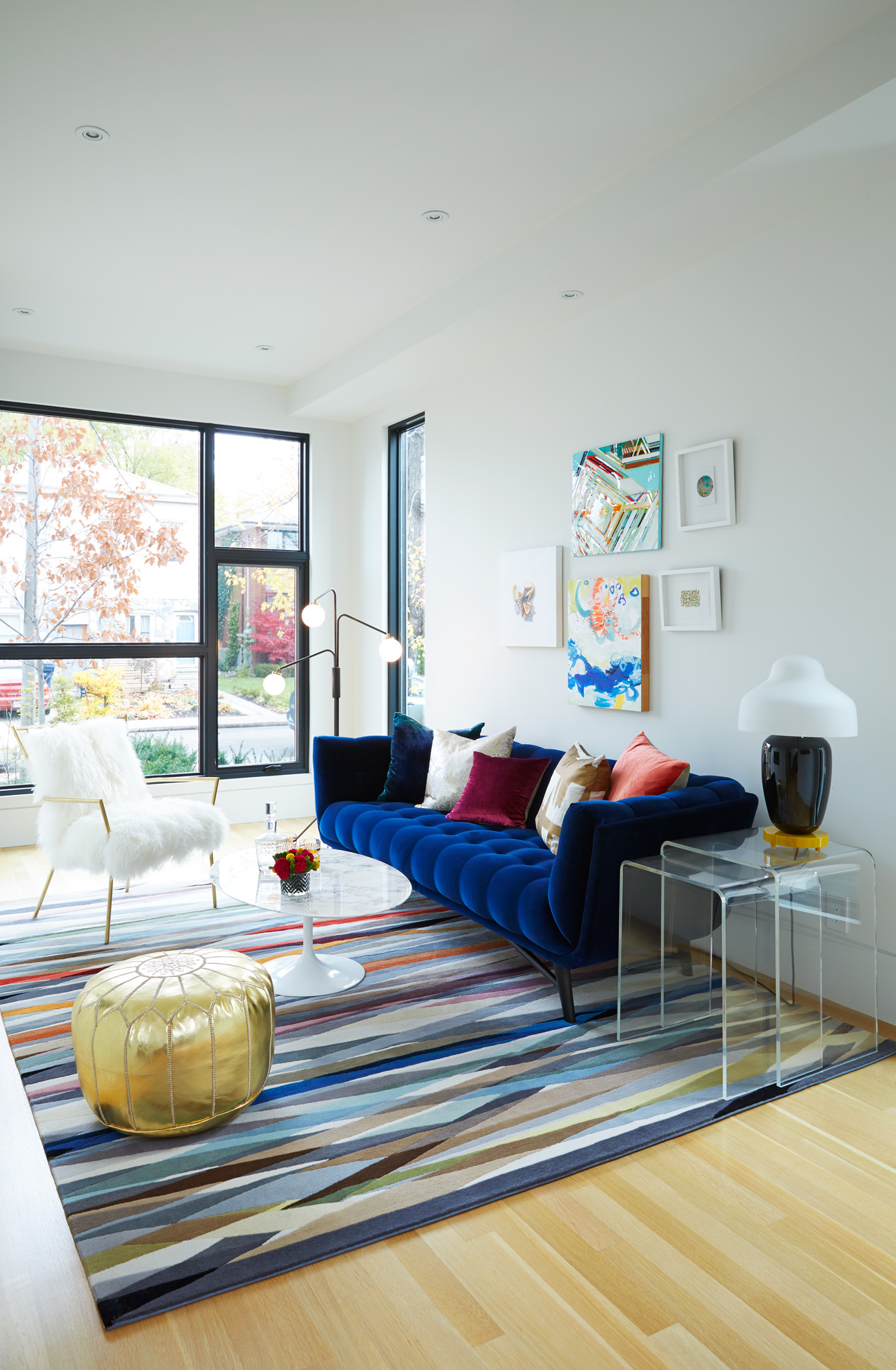 A grid of front windows frames the street. In the salon-style living room: rug and floor lamp from Avenue Road; table lamp from Lightform; chair, pouf and pillows from Elte; sofa by Roche Bobois; art from Art Interiors.