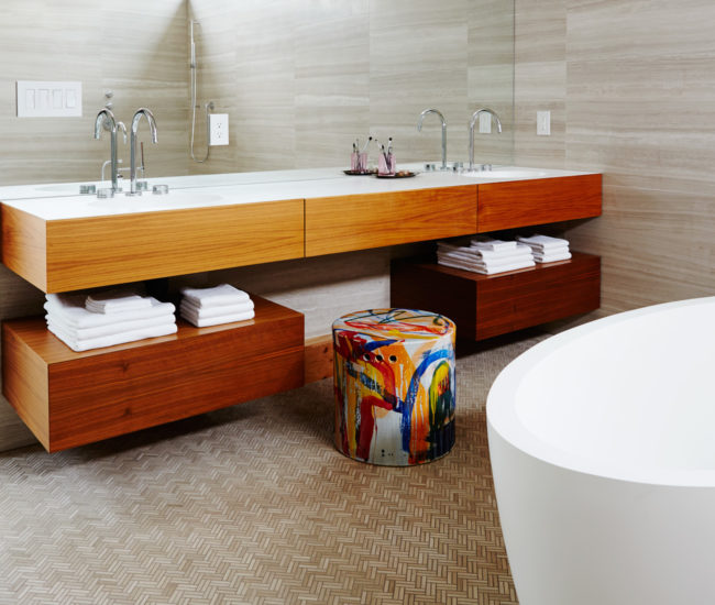 The heated floor slopes to a linear drain at the back of the master bath. The quartz soaker and all tile is from Tiles Plus; stool from Hollace Cluny. Mirror and Corian-topped floating vanity are custom.