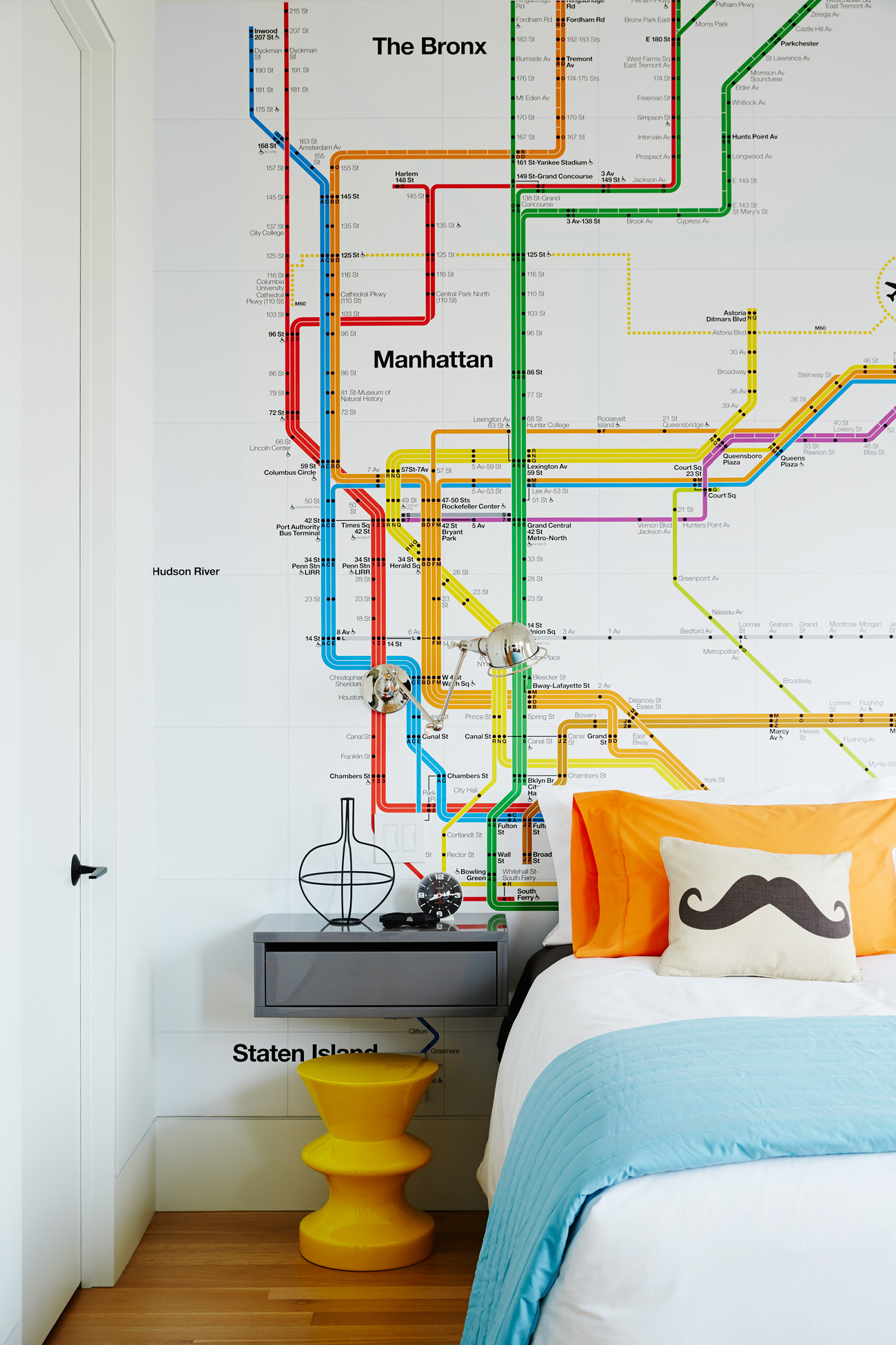 In keeping with the rest of the house, the son's second-floor bedroom is tastefully lively. Davey covered one wall with a NewYork transit map by Rollout. Bedding by AuLit; nightstand from CB2.