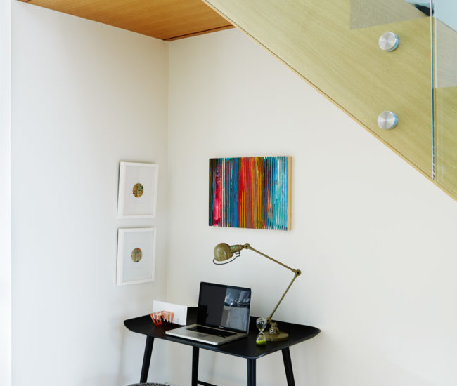 A small office is set up in the nook below the stairs. Desk and stool from Klaus; lamp from Hollace Cluny; art from Art Interiors.