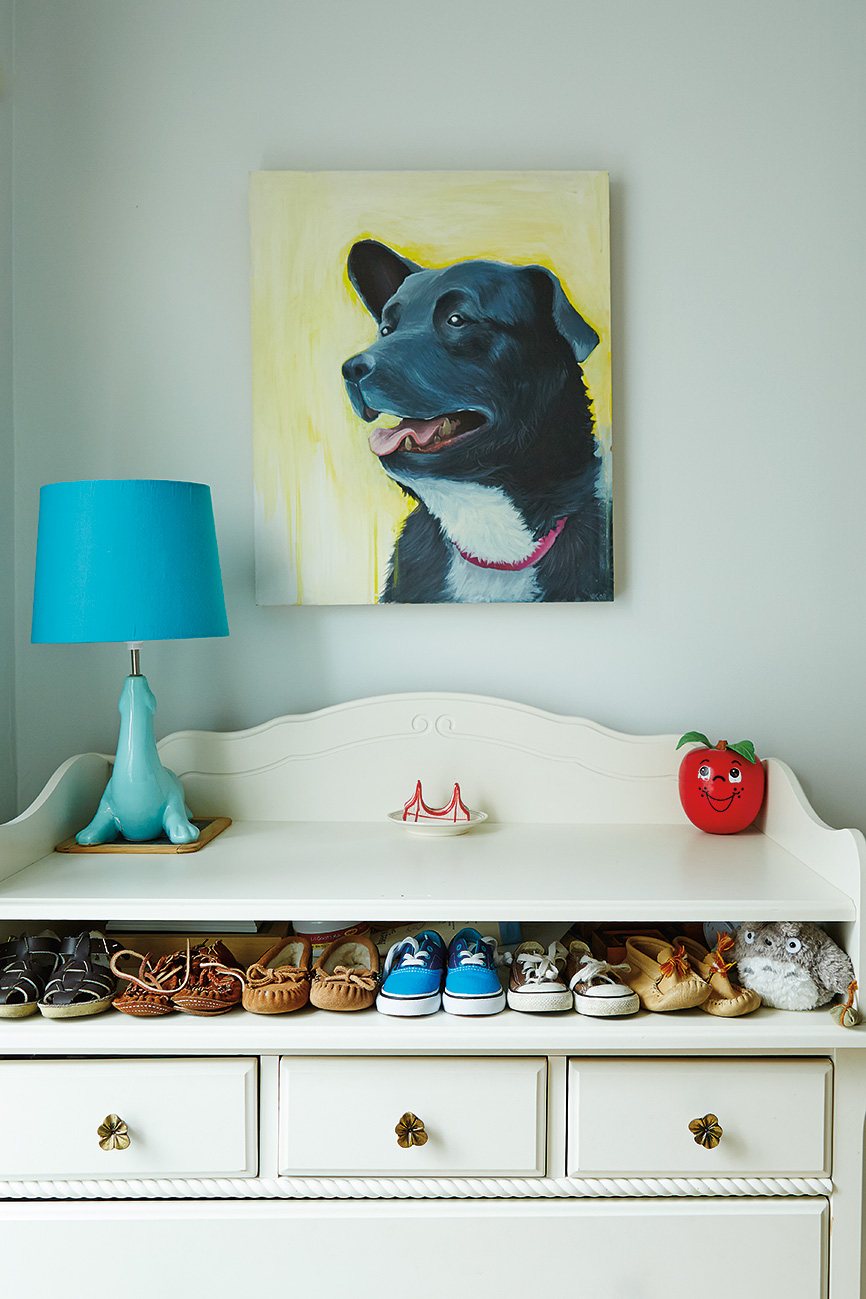 Above one-year-old Selby's dresser is a portrait of the family dog, Lucy, by Toronto artist Vlad Kato. Lamp from Urban Outfitters.