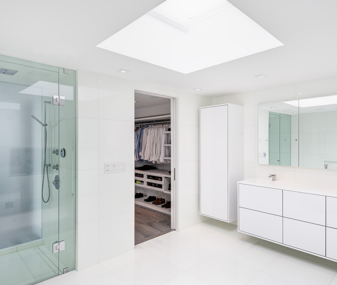 The master bath features a walk-in shower, a Poliform closet and a custom vanity. Floor-to-ceiling quartz tile from Stone Tile.