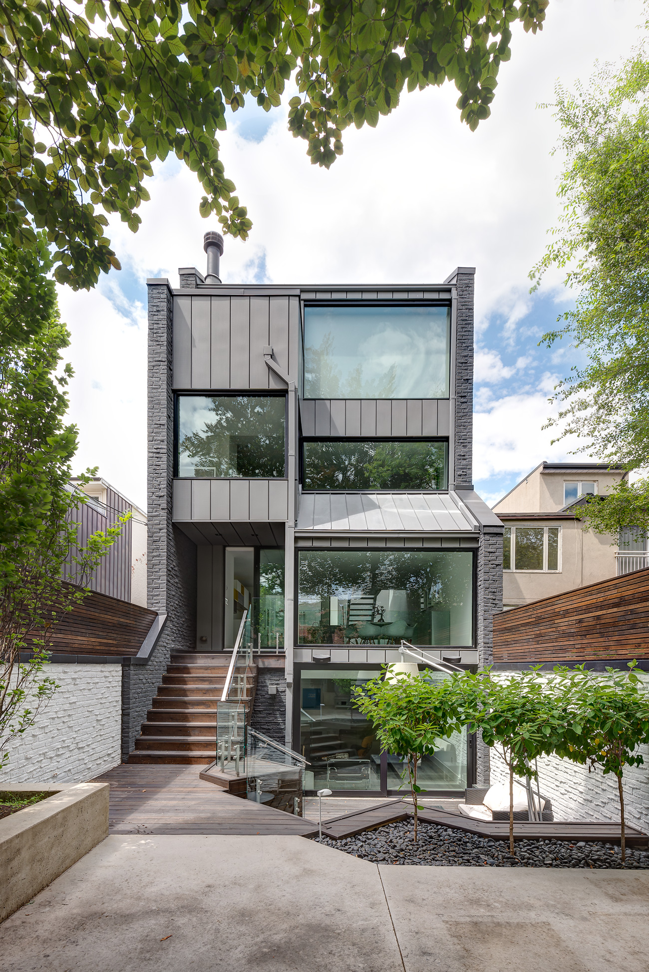Audax Architecture landscaped the 71-square-metre outdoor living space using poured concrete and stained cedar. The basement has a walk-out patio, and there is a private deck off the master bedroom.