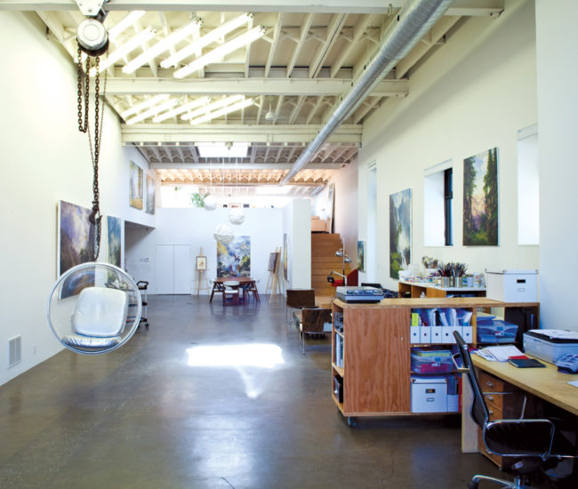 A 1960s-style bubble chair is suspended from an industrial winch, and Monkman's painted landscapes hang throughout the studio.
