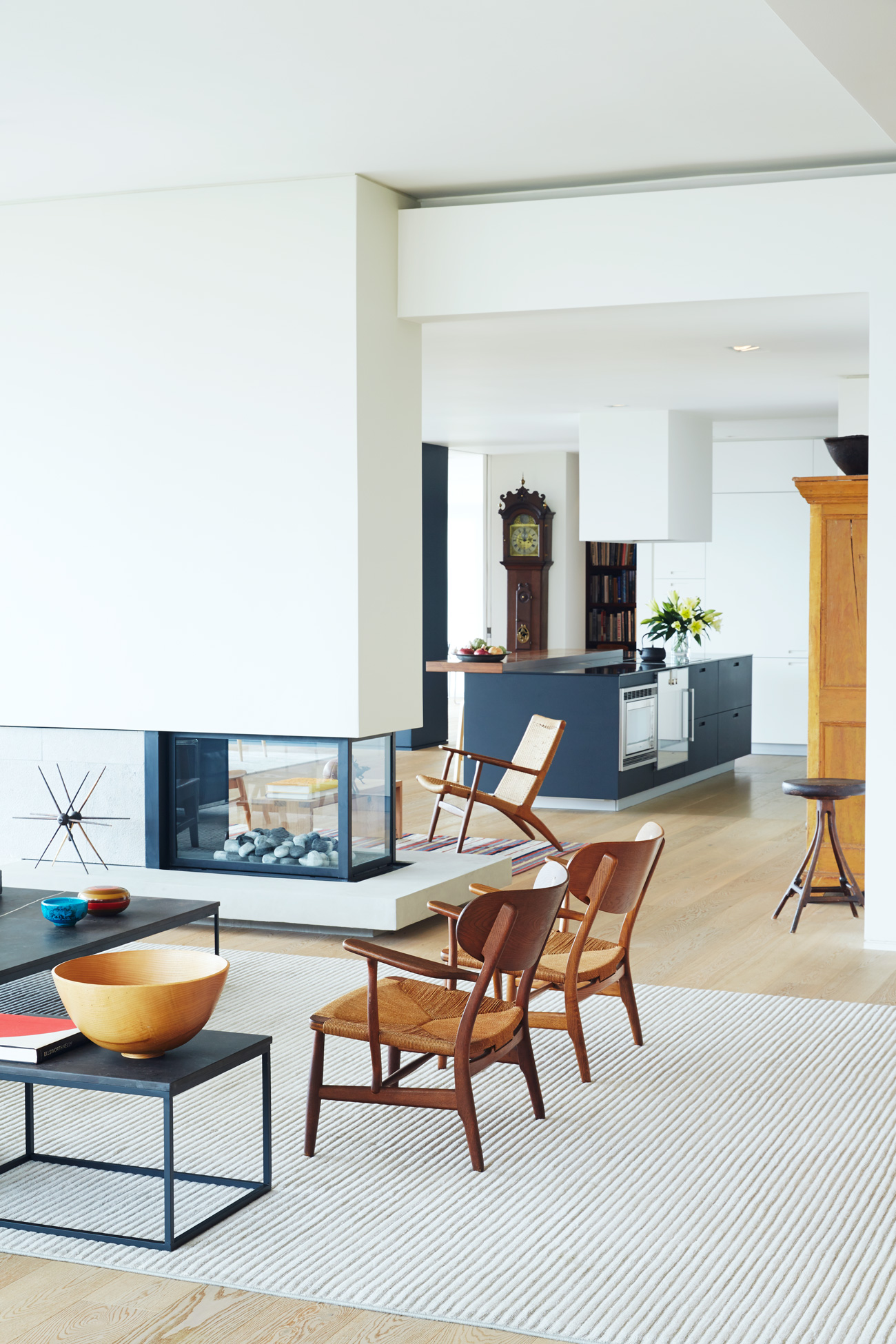 A dropped ceiling over the kitchen conceals the HVAC and trimless recessed lighting. It also makes the living room feel more grand. Engineered oak flooring throughout by Moncer. Vintage Hans Wegner chairs; rug from Elte.