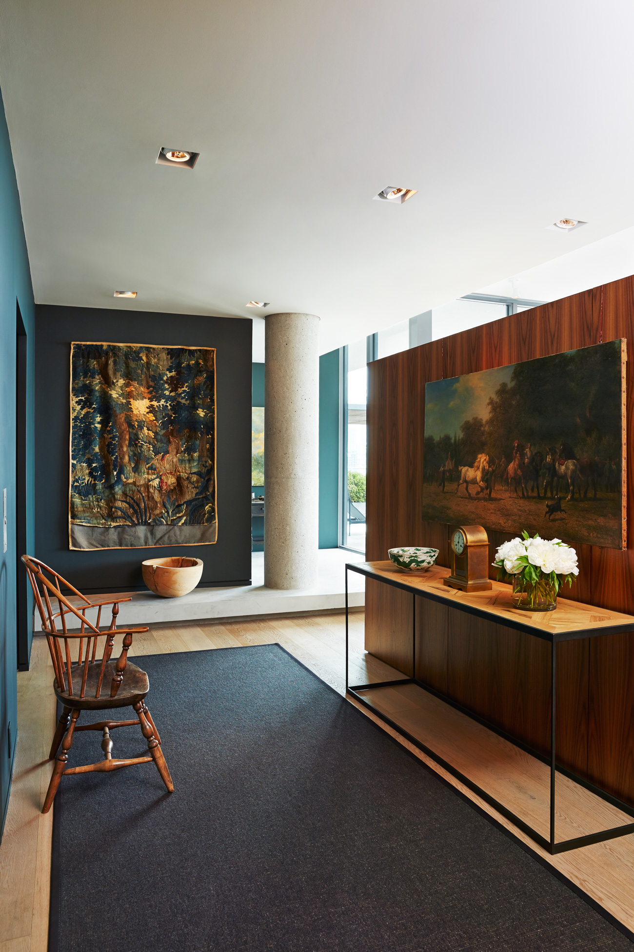 A partial walnut wall directs traffic off the foyer. Flemish tapestry, 17th-century; encaustic painting by Tony Scherman.