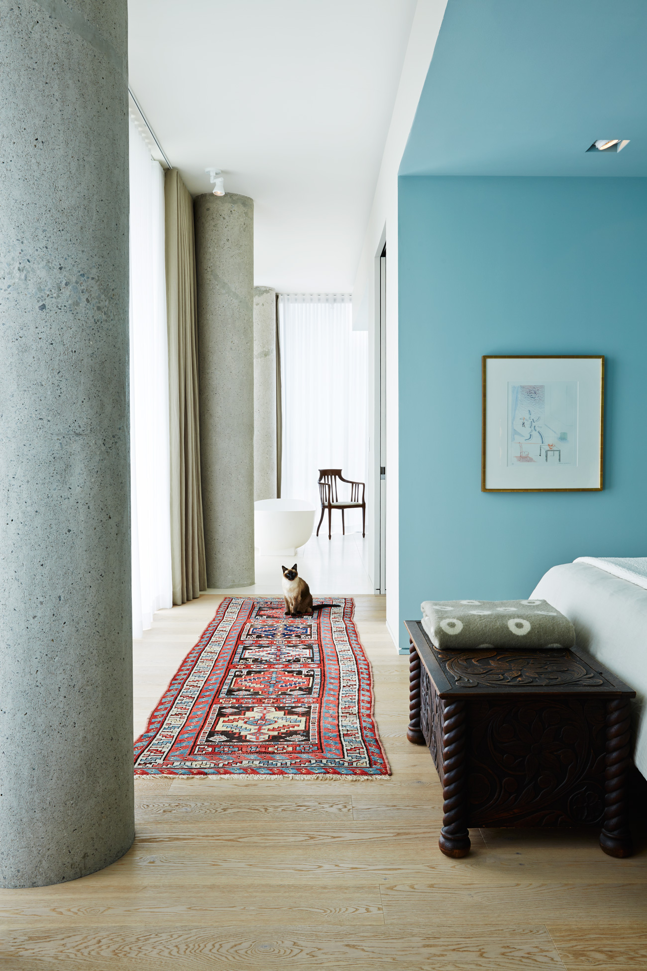 Facing north, just beyond the library, a long corridor links the sleeping area, walk-in closet and ensuite. Antique chest and Persian runner.