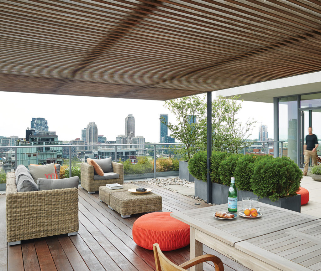 The rooftop terrace offers a nearly 360-degree view of the city. Flagstone, river stone and concrete pavers connect with decking and a pergola, both in ipe, to create outdoor rooms. Sofa, lounge chairs and dining table from D.O.T Furniture.