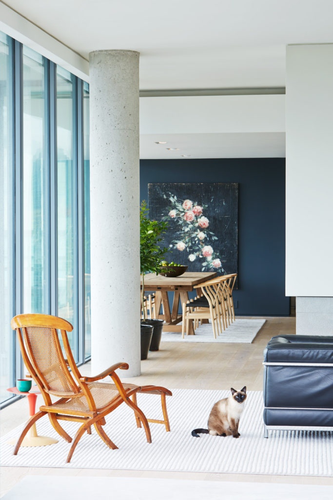 Artwork by Tony Scherman presides over Hans Wegner Wishbone chairs and a Restoration Hardware dining table.