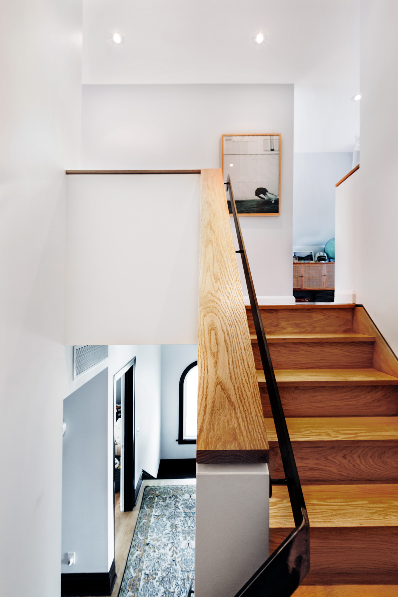 Stairs from the second floor to the master suite were widened and treated to oak treads and a custom railing by Mark Schnieder Enterprises.