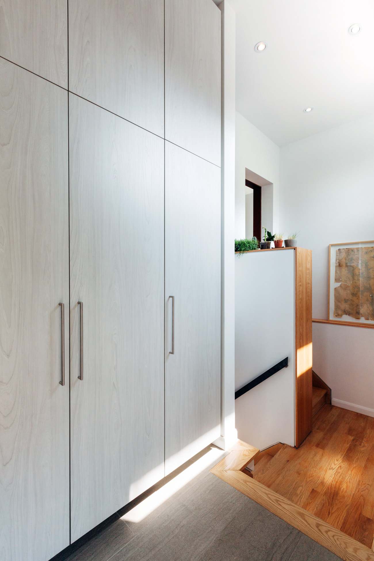 A former servery has made way for a mudroom with access to the basement and up to the kitchen. Closets for the family of five are fronted with textured laminate by Uniboard.