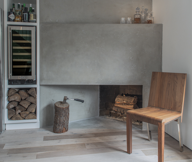 Its Summerhill project came with an interesting challenge: what to do with a 1970s chamfer corner fireplace? The new floor-to-ceiling design was fashioned from engineered cementitious concrete. Photo by Sean McBride.