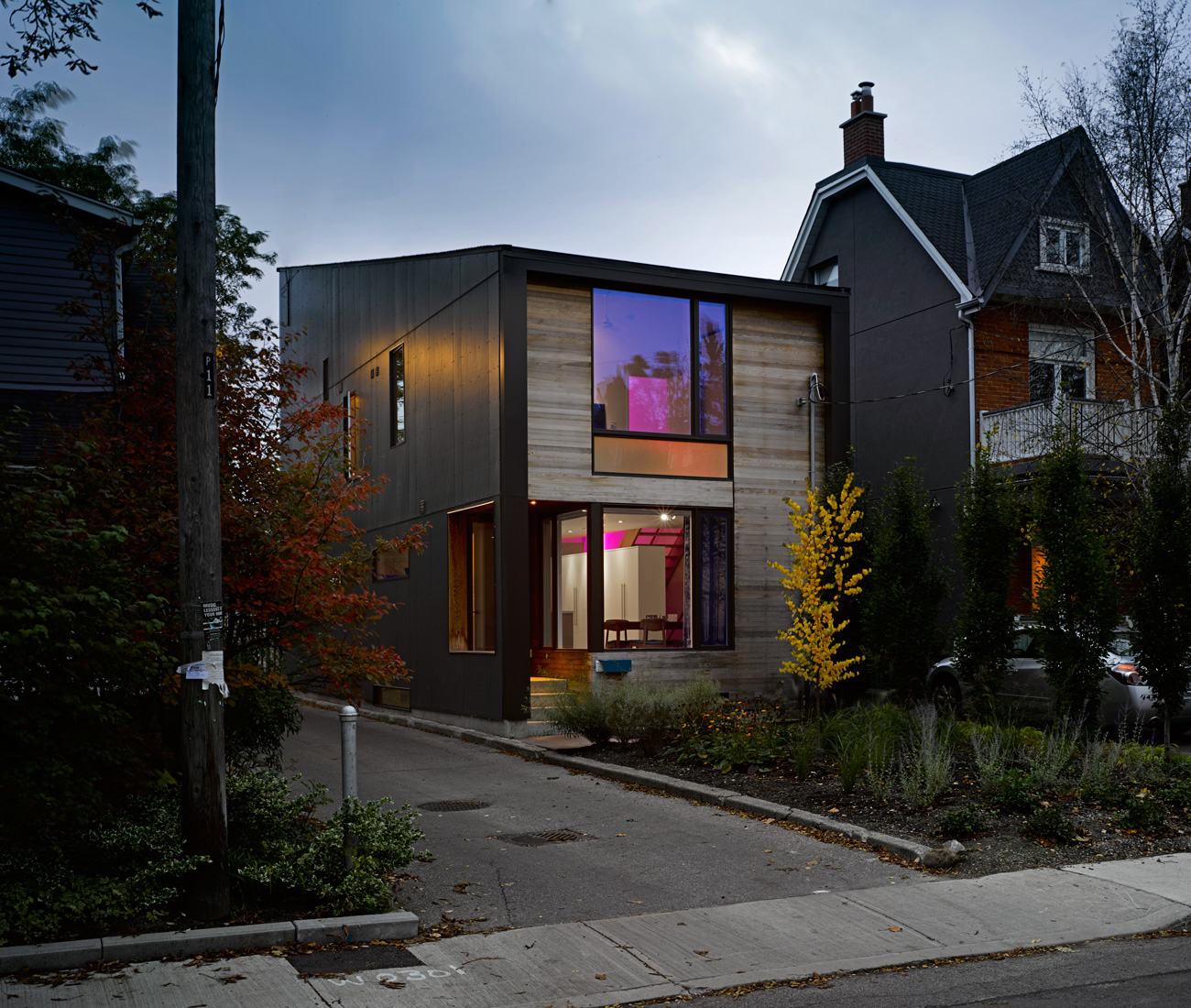Colourful LEDs light up the little Hardie-board and cedar-clad home's clerestory.