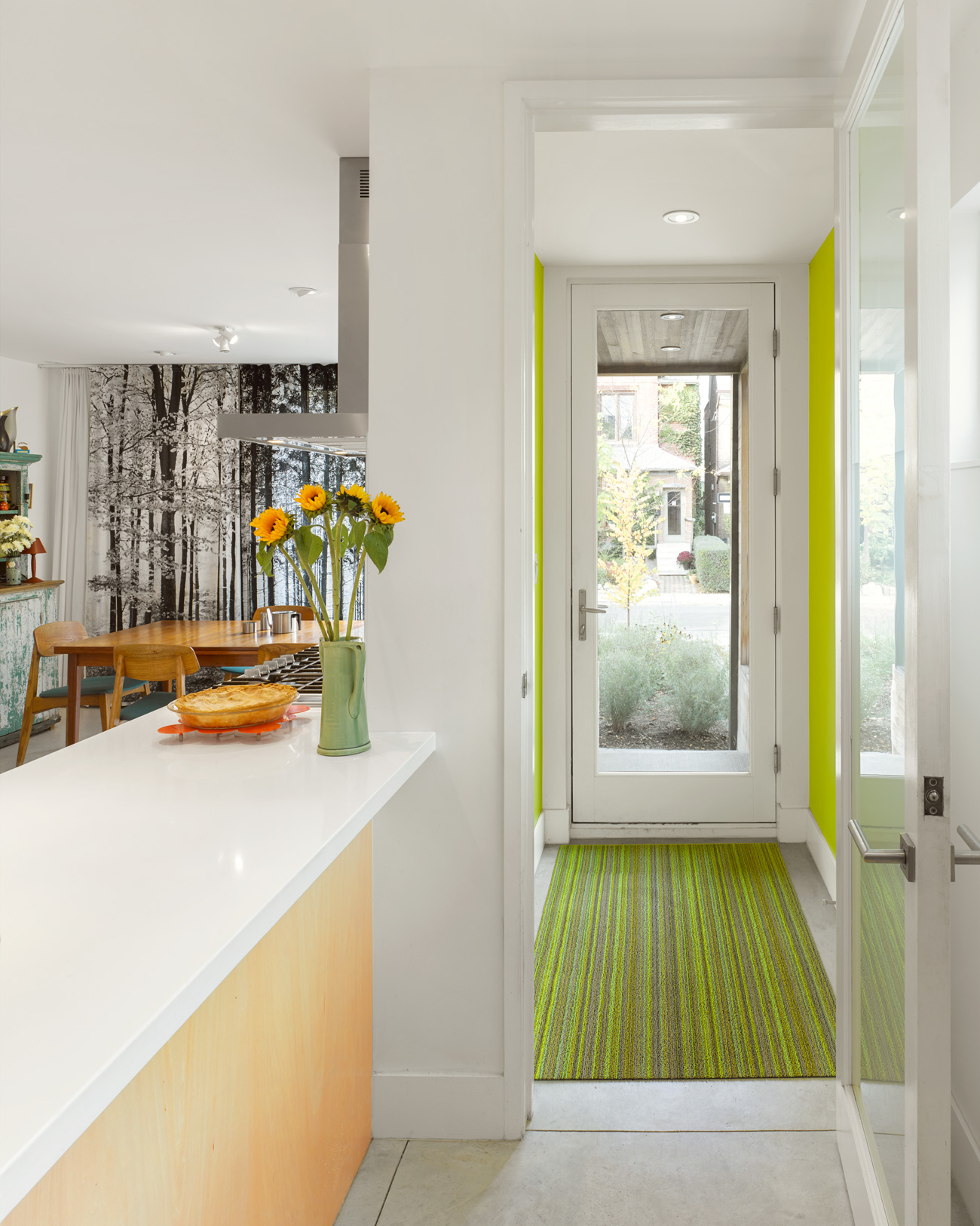 A Chilewich rug in the foyer leads to a vibrant kitchen.
