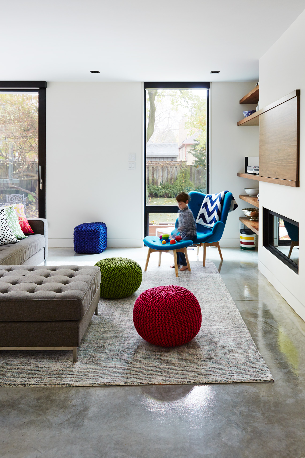 A walnut shelving unit branches out with a sliding TV cover. Sofa from Stylegarage; rug from Elte Market; windows by Ridley.