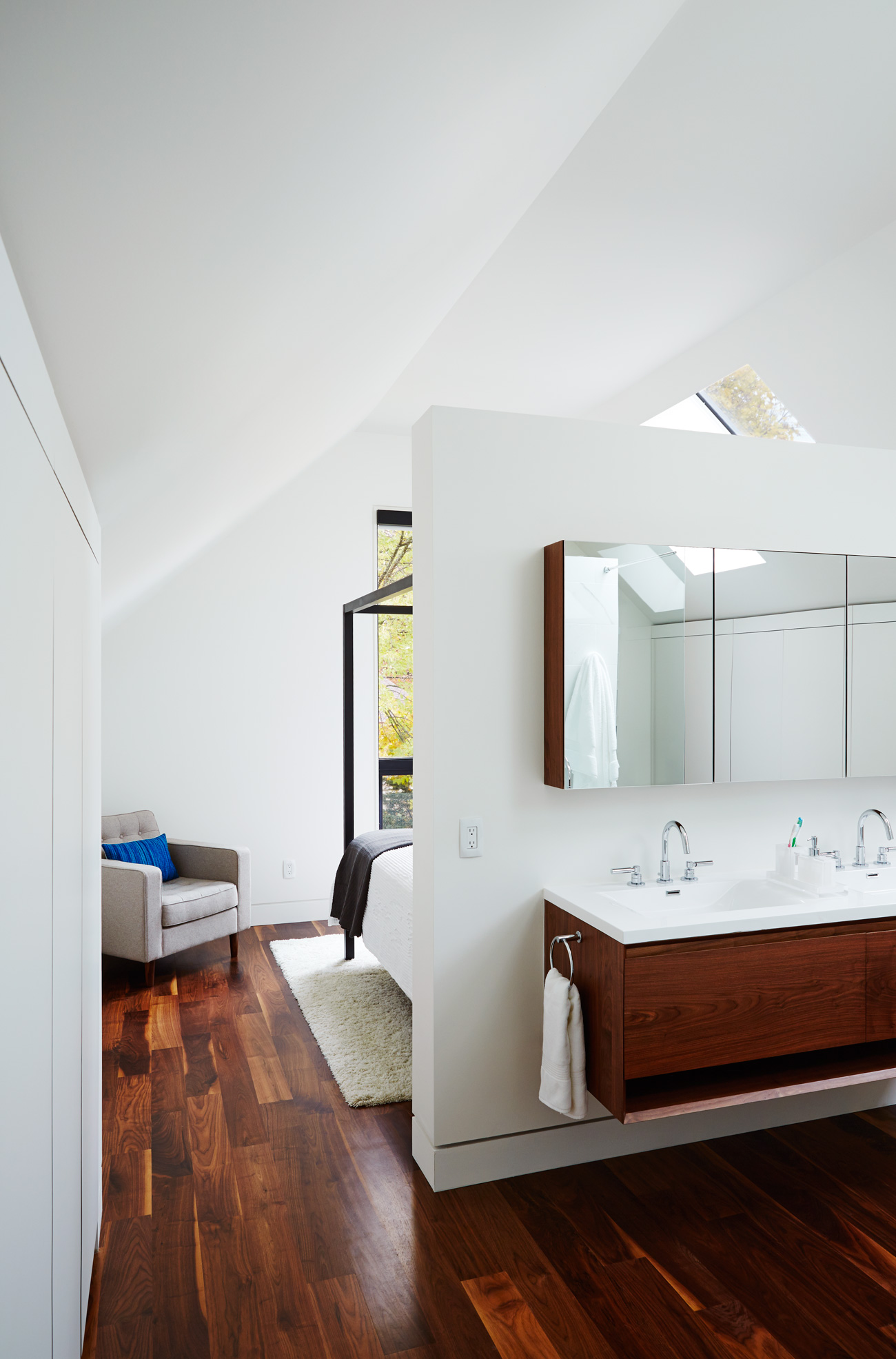 Velux skylights illuminate the cathedral space. Custom vanity with seamless countertop by Rubi; chair from EQ3; bed from Room and Board.