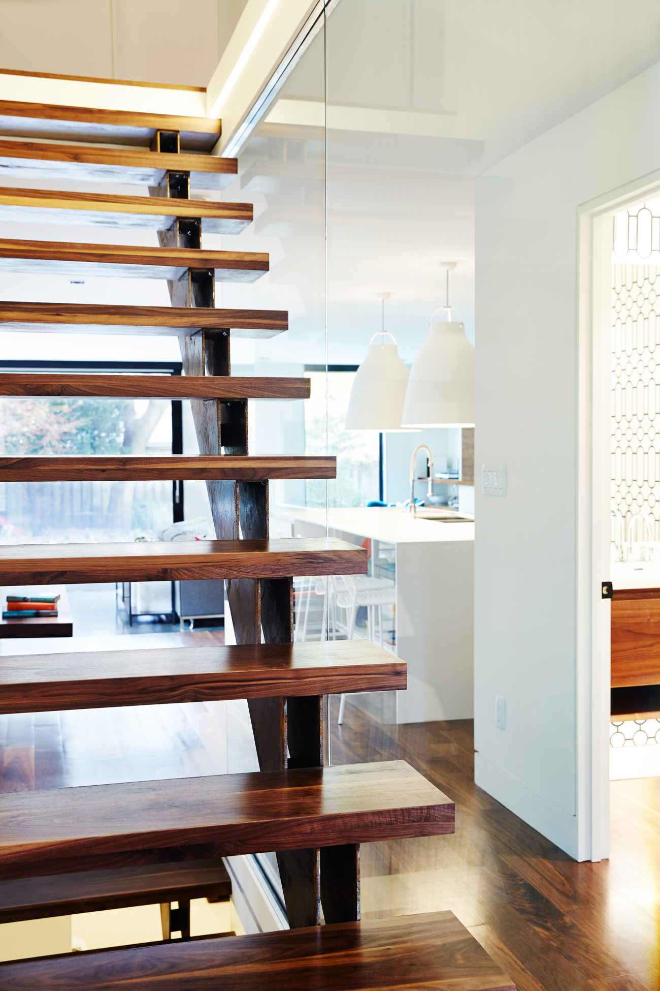 The open-tread staircase with two single stringers and glass railing spans three storeys and offers views from the foyer to the backyard.