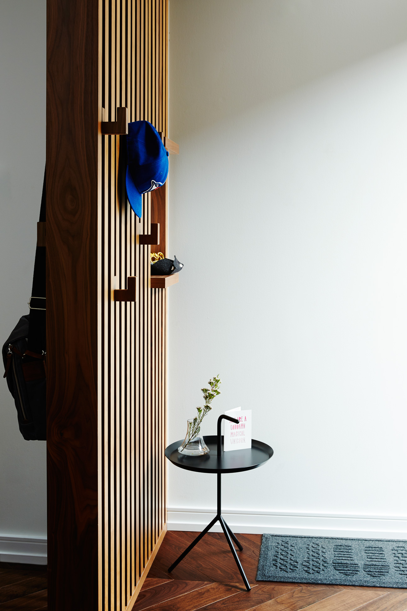 To create a foyer in the tiny entrance, Milne designed a walnut screen with vertical coat hooks. Side table from Klaus.